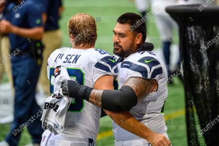 Seattle Seahawks offensive guard Mike Iupati (70) embraces Seattle Seahawks tight end Greg Olsen (88) before an NFL football game against the Atlanta Falcons, in Atlanta. The Seattle Seahawks won 38-25