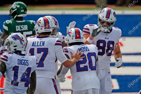 Buffalo Bills quarterback Josh Allen (17) celebrates with running back Zack Moss (20) after a touchdown during the first half of an NFL football game against the New York Jets in Orchard Park, N.Y