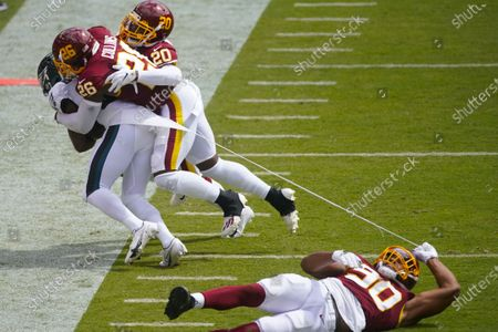 Washington Football Team defensive end Montez Sweat (90) falls while tearing a piece of of Philadelphia Eagles running back Jason Huntley's jersey who is being tackled by Washington Football Team strong safety Landon Collins (26) and cornerback Jimmy Moreland (20) during the first half of an NFL football game, in Landover, Md