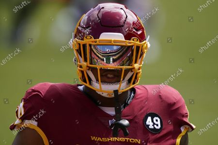 An empty Fedex Field is reflected in the visor of Washington Football Team nose tackle Daron Payne before the start of an NFL football game against the Philadelphia Eagles, in Landover, Md