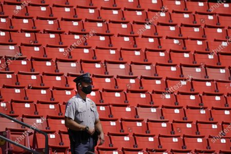 Stock Image of Prince George County Police Officer patrols a sections of empty seat at Fedex Field during the first half of an NFL football game between the Washington Football Team and Philadelphia Eagles, in Landover, Md