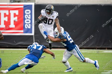 Jacksonville Jaguars running back James Robinson (30) leaps over Indianapolis Colts safety Khari Willis (37) and Indianapolis Colts middle linebacker Anthony Walker (54) during the second half of an NFL football game, in Jacksonville, Fla