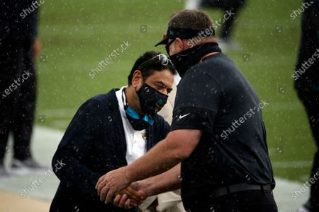 Jacksonville Jaguars owner Shahid Khan, left, greets head coach Doug Marrone before the start of an NFL football game against the Indianapolis Colts, in Jacksonville, Fla