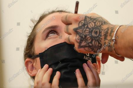 Model wearing a mask gets her make-up done in the backstage, prior to the Italian fashion designer Laura Biagiotti's spring-summer 2021/22 collection show, in Rome's Piazza del Campidoglio city council square