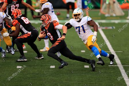 Cincinnati Bengals quarterback Joe Burrow (9) is chased by Los Angeles Chargers' Damion Square (71) during the second half of an NFL football game, in Cincinnati