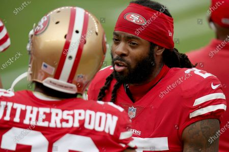 San Francisco 49ers' Richard Sherman (25) talks with San Francisco 49ers' Ahkello Witherspoon (23) on the sidelines during an NFL football game, in Santa Clara, Calif
