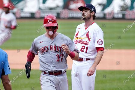 Cincinnati Reds' Tyler Stephenson, left, scores on a wild pitch by St. Louis Cardinals relief pitcher Andrew Miller, right, during the seventh inning of a baseball game, in St. Louis