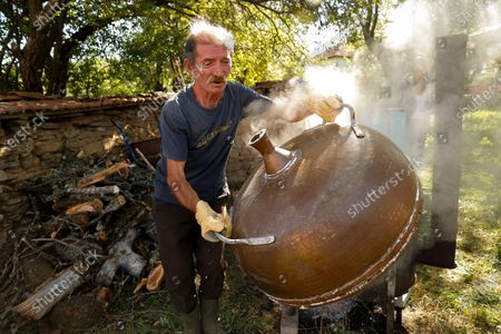 A Kosovar man makes home made brandy from fermented wild plums in their back yard by using an old owen in the village of Zebince, some 45 km east of the capital Pristina, Kosovo, 13 September 2020.