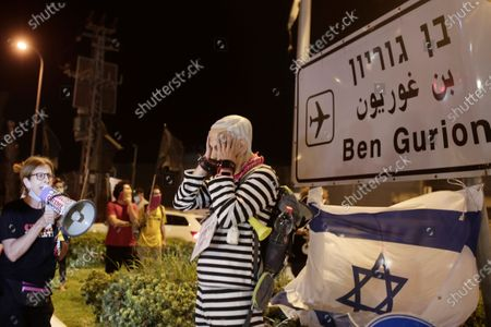 Protester wearing a rubber mask representing Israeli Prime Minister Benjamin Netanyahu stands at an entrance to Ben Gurion Airport, where Netanyahu and his family were expected to fly with an Israeli delegation to the U.S. for a ceremony with the United Arab Emirates, in Tel Aviv