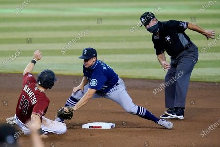 Stock Image of Seattle Mariners shortstop Donovan Walton, center, reaches over to tag out Arizona Diamondbacks' Josh VanMeter, left, at second base as umpire Rob Drake, right, looks on during the fifth inning of a baseball game, in Phoenix