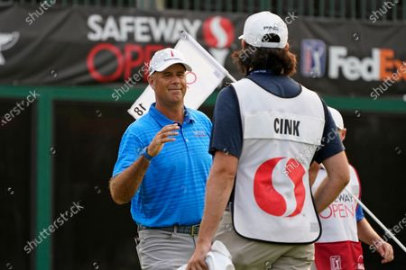 Stewart Cink greets his caddie and son, Reagan Cink, after making a birdie on the 18th green of the Silverado Resort North Course during the final round of the Safeway Open PGA golf tournament, in Napa, Calif. Cink won the tournament after shooting a 7-under-par 65 to finish at total 21-under-par