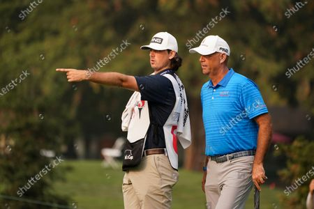 Stewart Cink and his son and caddie, Reagan Cink, read the 17th green of the Silverado Resort North Course during the final round of the Safeway Open PGA golf tournament, in Napa, Calif. Cink won the tournament after shooting a 7-under-par 65 to finish at total 21-under-par