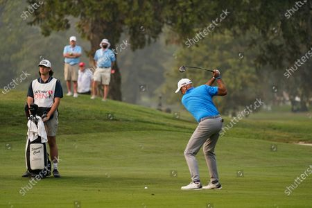 Stewart Cink hits from the 18th fairway of the Silverado Resort North Course during the final round of the Safeway Open PGA golf tournament, in Napa, Calif. Cink won the tournament after shooting a 7-under-par 65 to finish at total 21-under-par. At left is Cink's caddie and son, Reagan Cink