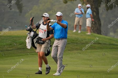 Stewart Cink walks with his caddie and son, Reagan Cink, down the 18th fairway of the Silverado Resort North Course during the final round of the Safeway Open PGA golf tournament, in Napa, Calif. Cink won the tournament after shooting a 7-under-par 65 to finish at total 21-under-par