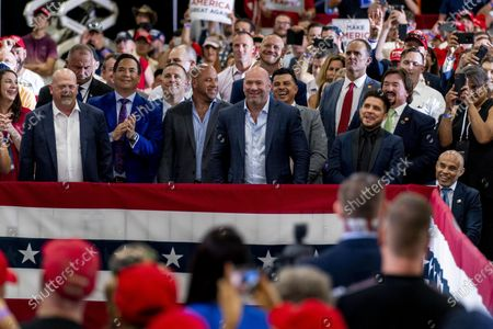 Stock Image of Dana White, head of the Ultimate Fighting Championship, center, accompanied by some Ultimate Fighting Championship fighters, listen as President Donald Trump speaks at a rally at Xtreme Manufacturing, in Henderson, Nev. Also pictured is Rick Harrison, who appears on the television show Pawn Stars, left