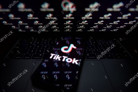 In this photo illustration a TikTok logo is seen displayed on a smartphone with the chinese flag in the background.