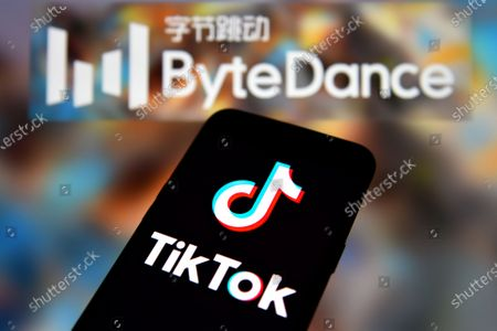 In this photo illustration a TikTok logo is seen displayed on a smartphone with the ByteDance logo in the background.