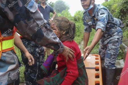 An injured girl is rescued after a landslide stuck early Sunday in Sindhupalchowk district, about 120 kilometers (75 miles) east of the capital, Kathmandu, Nepal, Monday, Sept.14, 2020. Rescuers resumed searching on Monday for people missing since a deadly landslide struck three villages in Nepal's mountains, authorities said