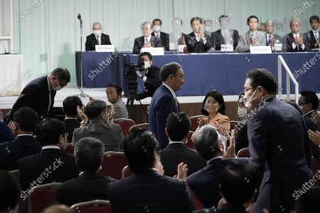 Former Defense Minister Shigeru Ishiba, left, and former Foreign Minister Fumio Kishida, right, bow after Japanese Chief Cabinet Secretary Yoshihide Suga, center, was elected as new head of Japan's ruling party the Liberal Democratic Party's (LDP) leadership election, September 14, 2020, in Tokyo. Tokyo, JAPAN 14 September 2020.
