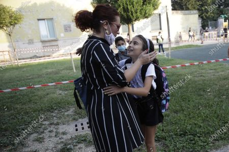 Stock Image of Maria Cristina Baggi greets her ten-year-old daughter Cecilia Rungi outside the San Biagio primary school in Codogno, Italy, . The morning bell Monday marks the first entrance to the classroom for the children of Codogno since Feb. 21, when panicked parents were sent to pick up their children after the northern Italian town gained notoriety as the first in the West to record local transmission of the coronavirus