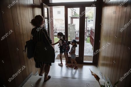 Maria Cristina Baggi, her daughters ten-year-old Cecilia Rungi and four-year-old Camilla, right, leave on their way to school in Codogno, Italy, . The morning bell Monday marks the first entrance to the classroom for the children of Codogno since Feb. 21, when panicked parents were sent to pick up their children after the northern Italian town gained notoriety as the first in the West to record local transmission of the coronavirus