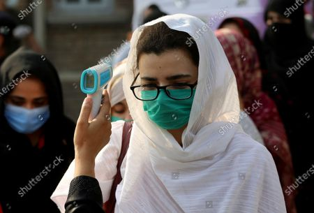 An official checks the body temperature of students at an entry point to Benazir Bhutto Women University for an examination ahead the university reopening that was closed since March, in Peshawar, Pakistan, . Education officials in Pakistan say authorities will start reopening educational institutions from Sept. 15 amid a steady decline in coronavirus deaths and infections