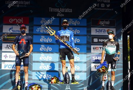 British rider Simon Yates (C) of the Mitchelton - Scott team celebrates with the trophy on the podium after winning the overall classification of the 55th Tirreno-Adriatico 2020 cycling race in San Benedetto del Tronto, Italy, 14 September 2020. Yates won ahead of second placed compatriot Geraint Thomas (L) of the Ineos Grenadiers team and third placed Polish rider Rafal Majka (R) of the Bora-Hansgrohe team.