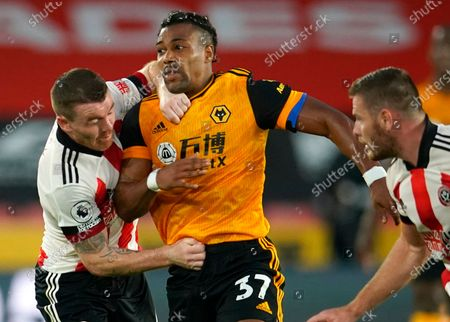 Sheffield's Jack O'Connell (L) in action against Wolverhampton's Adama Traore (C) during the English Premier League soccer match between Sheffield United and Wolverhampton Wanderers in Sheffield, Britain, 14 September 2020.