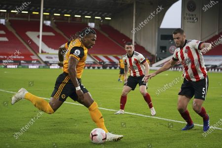 Wolverhampton Wanderers' Adama Traore, left, vies for the ball with Sheffield United's Jack O'Connell during the English League Cup soccer match between Sheffield United and Wolves at Bramall Lane stadium in Sheffield, England