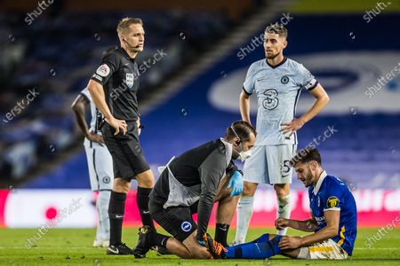 Stock Image of Brighton & Hove Albion Midfielder Adam Lallana (14) injured and receiving treatment looked on by Craig Pawson (Referee) & Chelsea Midfielder Jorginho (5) during the Premier League match between Brighton and Hove Albion and Chelsea at the American Express Community Stadium, Brighton and Hove
