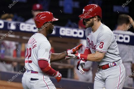 Philadelphia Phillies' Andrew McCutchen (22) celebrates with Bryce Harper (3) after scoring on a solo home run during the first inning of a baseball game against the Miami Marlins, in Miami