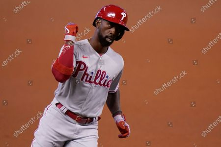 Philadelphia Phillies' Andrew McCutchen reacts as he rounds the bases after hitting a solo home run during the first inning of a baseball game against the Miami Marlins, in Miami
