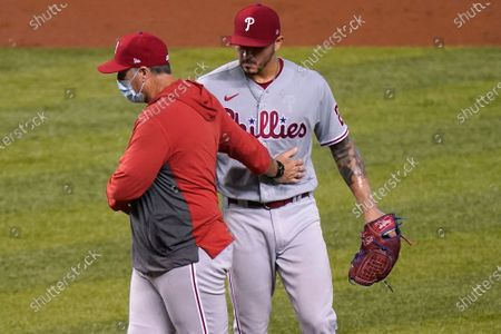Stock Photo of Philadelphia Phillies pitching coach Bryan Price, left, talks with starting pitcher Vince Velasquez as the base are loaded during the second inning of a baseball game against the Miami Marlins, in Miami