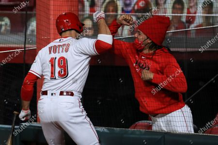 Cincinnati Reds' Joey Votto, left, reacts with Luis Castillo, right, after hitting a solo home run in the third inning during a baseball game against the Pittsburgh Pirates in Cincinnati