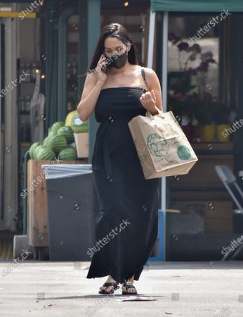 Nikki Bella talks on her phone as she leaves Whole Foods