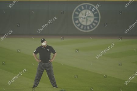 Second base umpire Bill Miller wears a mask as he stands on the field in air hazy from wildfire smoke during the first baseball game of a doubleheader between the Seattle Mariners and the Oakland Athletics, in Seattle