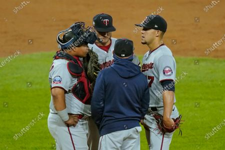 Minnesota Twins pitching coach Wes Johnson, center, talks with catcher Willians Astudillo, left, Josh Donaldson, and starting pitcher Jose Berrios, right, during the second inning of a baseball game against the Chicago White Sox, in Chicago
