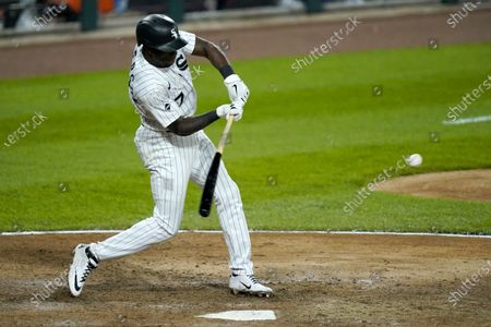 Chicago White Sox's Tim Anderson swings into an RBI-double off Minnesota Twins relief pitcher Taylor Rogers during the eighth inning of a baseball game, in Chicago. Luis Robert scored on the play