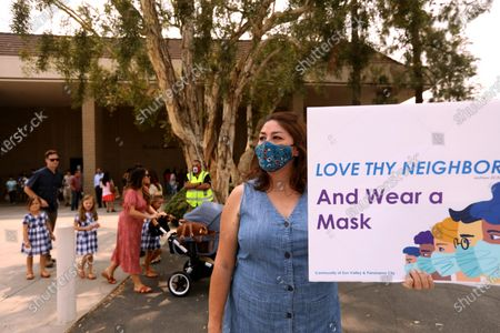SUN VALLEY, CA - SEPTEMBER 13, 2020 - - Sun Valley resident Aurora Perez, 50, reminds parishioners of Grace Community Church to wear a mask to prevent the spread of the coronavirus in front of the church in Sun Valley on September 13, 2020. Perez, who lives close to the church, has been a one-woman protest outside the church for several weeks. The Grace Community Church held a packed morning service Sunday, defying a court order directing them to refrain from holding indoor services due to the COVID-19 pandemic in Sun Valley. L.A. County Superior Court Judge Mitchell Beckloff sided with public health officials, who took legal action last month to enforce health orders against Grace Community Church, an evangelical congregation that has been holding Sunday worship services indoors since July 26. The majority of the parishioners refused to wear a mask.(Genaro Molina / Los Angeles Times)