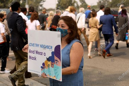Stock Photo of SUN VALLEY, CA - SEPTEMBER 13, 2020 - - Sun Valley resident Aurora Perez, 50, reminds parishioners, in background, of Grace Community Church to wear a mask to prevent the spread of the coronavirus in front of the church in Sun Valley on September 13, 2020. Perez, who lives close to the church, has been a one-woman protest outside the church for several weeks. The Grace Community Church held a packed morning service Sunday, defying a court order directing them to refrain from holding indoor services due to the COVID-19 pandemic in Sun Valley. L.A. County Superior Court Judge Mitchell Beckloff sided with public health officials, who took legal action last month to enforce health orders against Grace Community Church, an evangelical congregation that has been holding Sunday worship services indoors since July 26. The majority of the parishioners refused to wear a mask. (Genaro Molina / Los Angeles Times)
