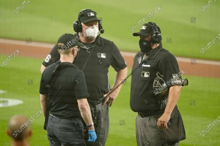 Home plate umpire Doug Eddings, right, and second base umpire Bill Miller, center, wear masks as they stand with a replay technician, left, as they review a play during the first baseball game of a doubleheader between the Seattle Mariners and the Oakland Athletics, in Seattle