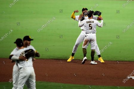San Diego Padres shortstop Fernando Tatis Jr., back left, celebrates with Greg Garcia after the team defeated the Los Angeles Dodgers in a baseball game, in San Diego