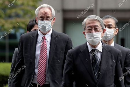 Former Nissan Motor Co. executive Greg Kelly, left, arrives for the first trial hearing at the Tokyo District Court in Tokyo . The financial misconduct trial of Kelly opened Tuesday. Japanese prosecutors outlined allegations of what they said was a complex and clandestine scheme to pay former star executive Carlos Ghosn