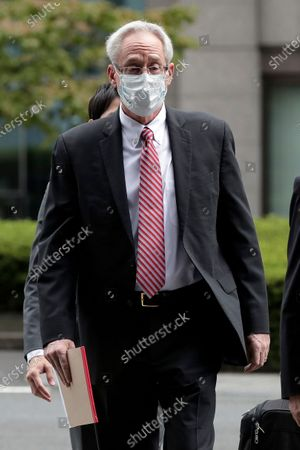 Former Nissan Motor Co. executive Greg Kelly arrives for the first trial hearing at the Tokyo District Court in Tokyo . The financial misconduct trial of Kelly opened Tuesday. Japanese prosecutors outlined allegations of what they said was a complex and clandestine scheme to pay former star executive Carlos Ghosn