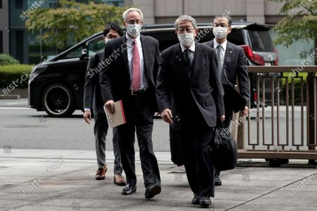 Former Nissan Motor Co. executive Greg Kelly, left in foreground, arrives for the first trial hearing at the Tokyo District Court in Tokyo . The financial misconduct trial of Kelly opened Tuesday. Japanese prosecutors outlined allegations of what they said was a complex and clandestine scheme to pay former star executive Carlos Ghosn