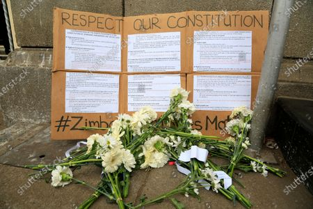 Flowers are placed outside the High Court during a peaceful protest by Zimbabwe lawyers over abuse of power by the courts in Harare, . Human rights defenders say it appears the government is using restrictions imposed to combat COVID-19 to suppress political criticism. Opposition officials, human rights groups and some analysts accuse Mnangagwa of abusing the rights of critics, using tactics as harsh as his predecessor, the late Robert Mugabe