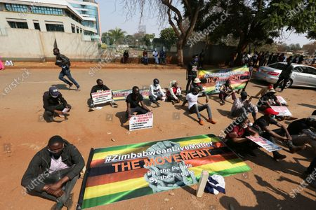 Students and human rights activists take part in a peaceful protest in Harare, . Human rights defenders say it appears the government is using restrictions imposed to combat COVID-19 to suppress political criticism. Opposition officials, human rights groups and some analysts accuse Mnangagwa of abusing the rights of critics, using tactics as harsh as his predecessor, the late Robert Mugabe
