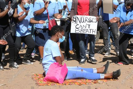 Nurse sits on the ground during a protest over poor working conditions and lack of adequate PPE for health personnel in this photo. Human rights defenders say it appears the government is using restrictions imposed to combat COVID-19 to suppress political criticism. Opposition officials, human rights groups and some analysts accuse Mnangagwa of abusing the rights of critics, using tactics as harsh as his predecessor, the late Robert Mugabe
