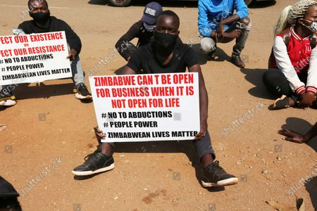 Student and human rights activist holds a banner during a peaceful protest in Harare, . Human rights defenders say it appears the government is using restrictions imposed to combat COVID-19 to suppress political criticism. Opposition officials, human rights groups and some analysts accuse Mnangagwa of abusing the rights of critics, using tactics as harsh as his predecessor, the late Robert Mugabe