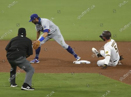Greg Garcia of the San Diego Padres slides into second base as Chris Taylor of the Los Angeles Dodgers tries to catch the ball in the 7th inning at Petco Park on Monday, Sept. 14, 2020 in San Diego, CA